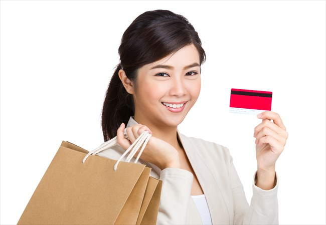 Woman holding credit card and shopping bag