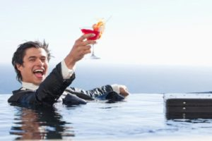 Delighted businessman relaxing in a swimming pool with a cocktail